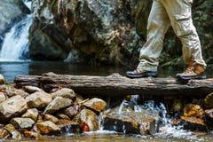 Приключение концепции образа жизни перемещения влажных ботинок пешее, пересекает поток стоковые фото