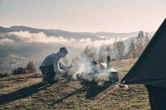 приключение осени Молодой человек делая лагерный костер пока сидящ близко Стоковые Фото