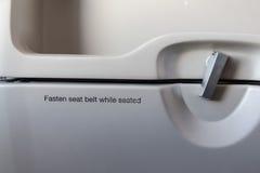 Прикрепите ремень безопасности пока усаженный знак на самолете стоковое фото rf