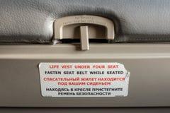 Прикрепите ремень безопасности пока усаженный символ на задней части места самолета стоковые изображения rf