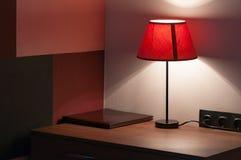 Прикроватный столик на котором ложь кожаная папка меню, не нарушает знак и лампу с абажуром ткани Стоковое Изображение