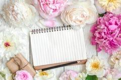 Прикройте выровнянную тетрадь в рамке цветка сделанной из розовых и белых пиона, роз и цветков и подарочной коробки жасмина Стоковые Изображения