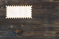 Прикройте высекаенную рамку на винтажной деревянной предпосылке Стоковое Фото
