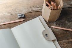 Прикройте ежедневную тетрадь плановика с карандашами и точилкой для карандашей o Стоковое Изображение