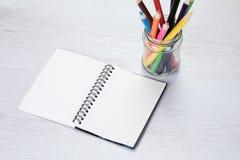 Прикройте открытую тетрадь с crayons карандаша Стоковые Изображения