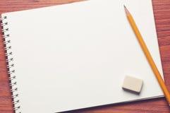 Прикройте раскрытый блокнот с карандашем и ластиком дальше Стоковая Фотография
