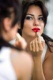 прикладывать косметическую женщину красного цвета губной помады стоковая фотография rf