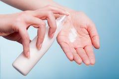 прикладывать политуру кожи внимательности прозрачную Женские ладони с moisturizing сливк Стоковое Фото