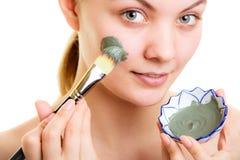прикладывать политуру кожи внимательности прозрачную Женщина прикладывая маску грязи глины на стороне стоковые изображения rf