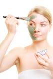 прикладывать политуру кожи внимательности прозрачную Женщина прикладывая маску грязи глины на стороне Стоковые Изображения