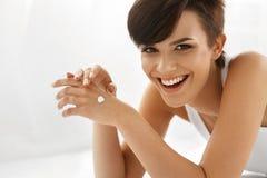 прикладывать политуру кожи внимательности прозрачную Красивая счастливая женщина с сливк руки, лосьоном в наличии стоковые фотографии rf