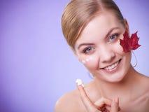 прикладывать политуру кожи внимательности прозрачную Сторона девушки молодой женщины с красным кленовым листом Стоковое фото RF