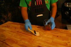 Прикладывать политуру на деревянную поверхность с щеткой Стоковое Изображение RF