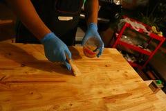 Прикладывать политуру на деревянную поверхность с щеткой Стоковые Фото