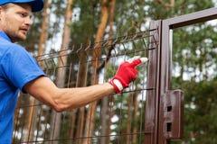 Приложение территории - работник устанавливая загородку металла стоковые изображения rf