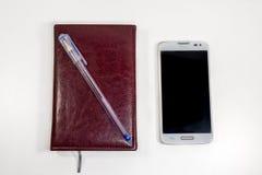 Примечание Брайна с ручкой и телефон на таблице Стоковая Фотография