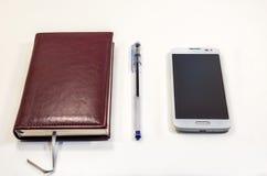 Примечание Брайна с ручкой и телефон на таблице стоковые изображения