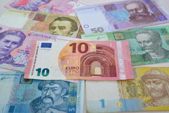 Примечание 10 евро лежит над украинскими бумажными деньгами, предпосылкой Стоковое Изображение RF