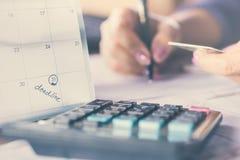 Примечание календаря крайнего срока с предпосылкой нерезкости сочинительства руки бизнес-леди на бумажной рассчитывать кредитной  Стоковое Изображение RF