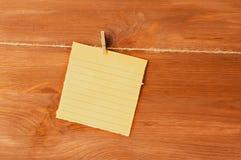 Примечание на деревянных зажимках для белья на предпосылке Стоковая Фотография