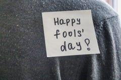 Примечание на задней части молодого человека с шуточным текстом Шутка первое -го апрель стоковое изображение