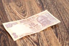 Примечание 10 рупий (индийская валюта) на деревянном Стоковое фото RF