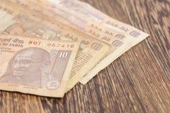 10 примечаний рупии (индийская валюта) на деревянном Стоковая Фотография RF