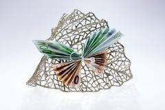 Примечания евро в форме бабочек на декоративных блестящих лист Стоковая Фотография