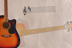Примечания и акустическая гитара sunburst на левой стороне грубой предпосылки картона Стоковые Изображения RF