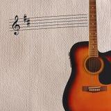 Примечания и акустическая гитара sunburst на правильной позиции грубой предпосылки картона Стоковая Фотография