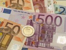 Примечания и монетки евро стоковые фото