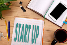 Примечания НАЧИНАЮТ ВВЕРХ в блокноте на столе бизнесмена Стоковое Изображение
