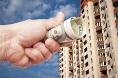 Примечания доллара США в руке против обитаемого в дома высоко-пола стоковое изображение rf