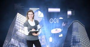 Примечания сочинительства женщины в тетради и высоких зданиях с накаляя интерфейсом статистик и диаграмм Стоковые Фотографии RF