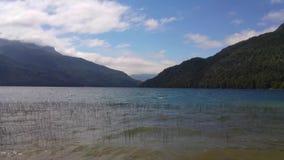 Примите в озеро при тростники приходя из воды Горы предпосылки и голубое небо, с облаками Волны в воде сток-видео