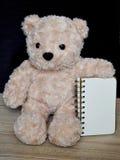 Принесите куклу и тетрадь на деревянной таблице стоковые изображения rf