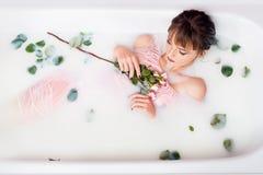 Принимает ванну с молоком и лепестками розы Обработки курорта для подмолаживания кожи стоковая фотография