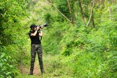 Принимать фотографа профессиональной женщины на открытом воздухе с основным объективом в зеленой природе дождевого леса джунглей стоковые фотографии rf