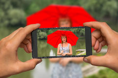 Принимать фото дамы с красным зонтиком с мобильным телефоном Стоковые Фото