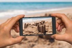 Принимать фото замка песка с мобильным телефоном Стоковое Изображение RF