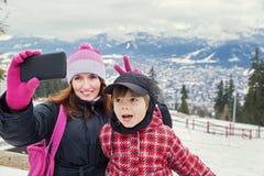 Принимать selfie! Семья Счастливая мать и мальчик делая автопортрет в горах зимы Стоковое Изображение