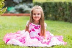 Принцесса девушки сидела на лужайке в зеленом саде Стоковые Изображения