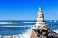 Принципиальная схема баланса и сработанности Белый дзэн утесов на предпосылке моря и голубого неба стоковые фотографии rf