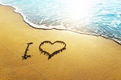 Принципиальная схема влюбленности на песке пляжа Стоковая Фотография