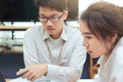 Принципиальная схема дела сыгранности Молодой азиатский работник 2 коллективно обсуждать совместно в современном офисе Концепция  Стоковая Фотография