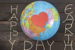 Принципиальная схема дня земли Карточка сердца бумажная кладет на глобус Стоковые Изображения RF