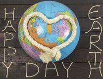 Принципиальная схема дня земли Сердце knoted с веревочкой кладет на глобус Стоковое Фото