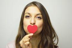 Принципиальная схема дня ` s Валентайн Портрет красивой девушки целуя ее малое бумажное сердце на серой предпосылке Стоковые Фотографии RF