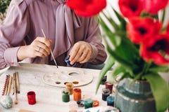принципиальная схема пасха счастливая руки держа и крася пасхальные яйца дальше Стоковые Изображения RF
