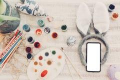принципиальная схема пасха счастливая уши и телефон зайчика с пустым экраном и Стоковые Изображения RF